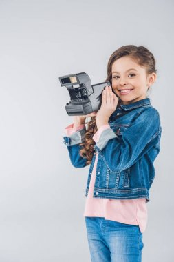Adorable girl with retro camera
