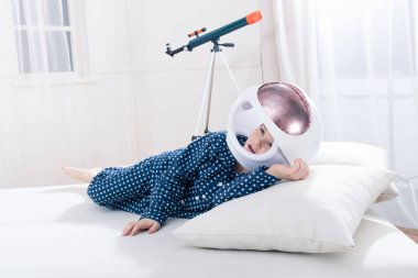 Cute little boy in pajamas and space helmet lying on pillow stock vector