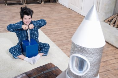 Excited little boy in pajamas sitting on carpet and launching rocket stock vector