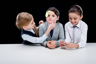 girls putting notes on boy's face