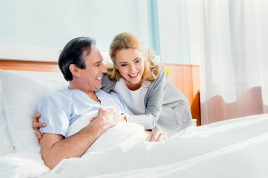 Happy wife visiting elderly husband in hospital stock vector