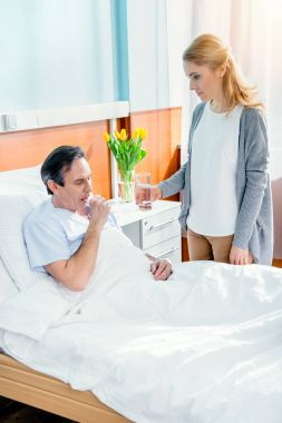 wife giving glass of water to husband