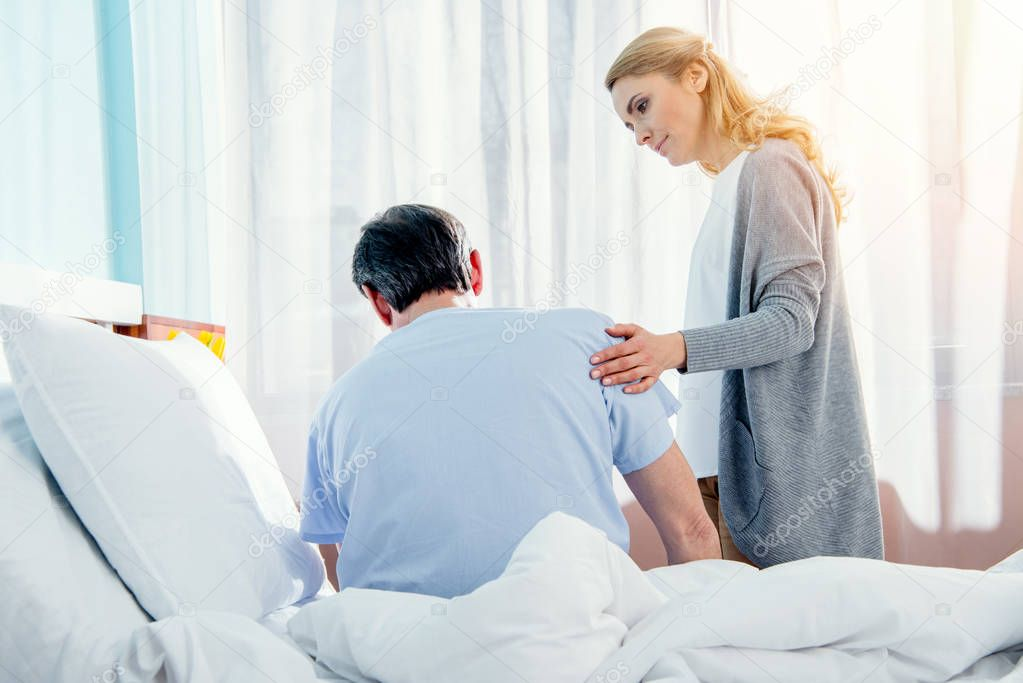 woman helping husband stand up