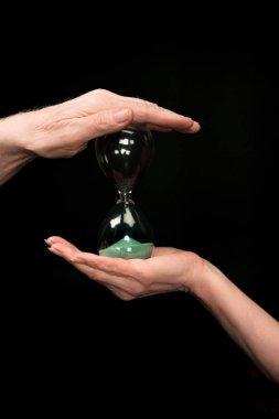 senior couple holding hourglass