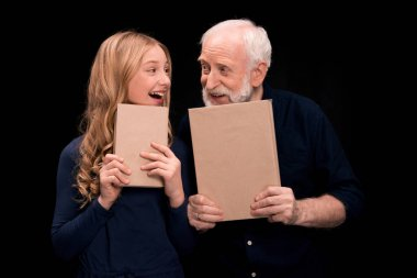 grandfather and granddaughter holding books