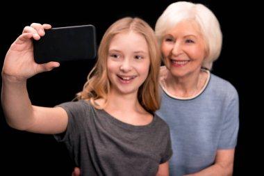 Grandmother and granddaughter taking selfie