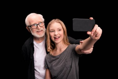 Grandfather and granddaughter taking selfie