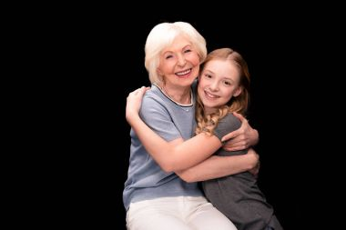 Happy grandmother and granddaughter hugging each other isolated on black stock vector