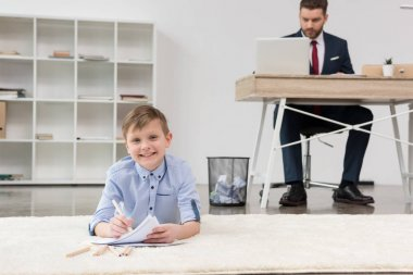 Boy drawing while his father working