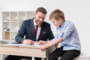 Businessman drawing on business papers with son