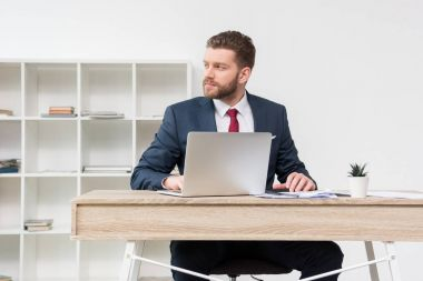 Confident businessman at table in office