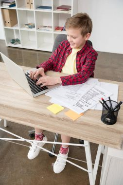 schoolboy using laptop at office