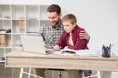 freelancer working at table with son