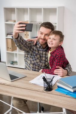 Businessman freelancer taking self portrait with son at home office stock vector