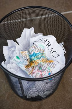 wrinkled business papers in trash bucket