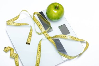 Close-up view of digital scales with green apple and measuring tape  isolated on white stock vector