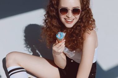 Girl in sunglasses eating ice cream