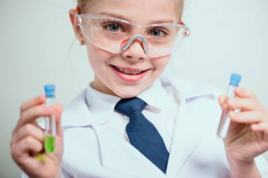 Schoolgirl in goggles holding reagents in flasks isolated on grey, science student concept stock vector