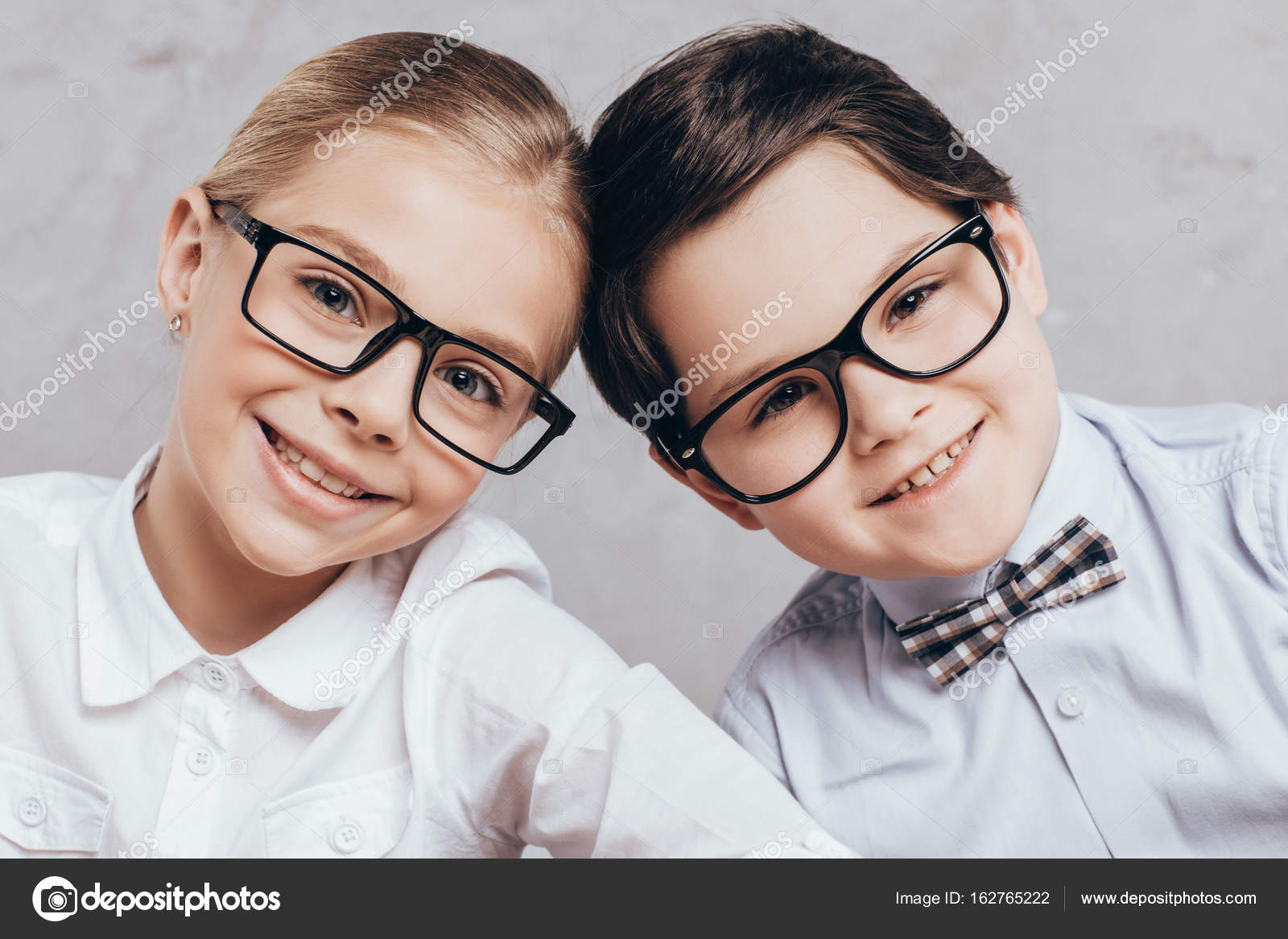 477372255e Retrato de sonriente pequeño chico y chica en gafas mirando a cámara -  fotos: niños con lentes — Foto de ...