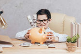 kid with piggy bank at workplace
