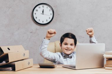 excited child at workplace with laptop