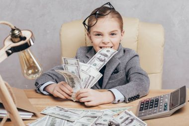 little child with money at workplace