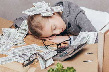 kid sleeping at workplace with money