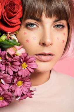 Young woman with stars on her face posing with bright flowers near her face and looking at camera stock vector