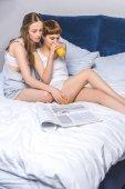 fiatal leszbikus pár ivás lé, és az olvasás, magazin, az ágyban