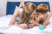 boldog fiatal leszbikus pár, cuddling in bed okostelefonok használata közben