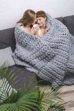 happy lesbian couple with cup of coffee embracing under knitted wool blanket on couch