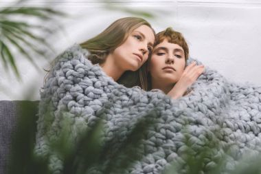young lesbian couple sitting under knitted wool blanket together and embracing