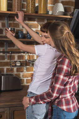 passionate young woman flirting with her girlfriend on kitchen