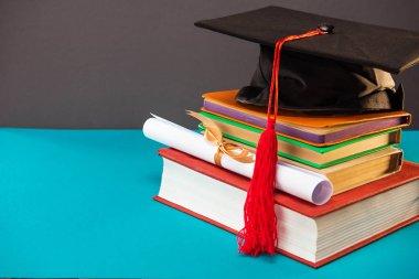 books, diploma and graduation cap