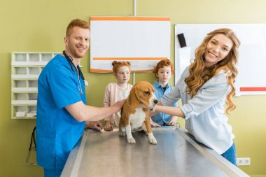 Woman, children with dog at veterinary doctor