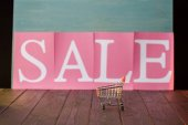 Fotografie small shopping cart with sale sign