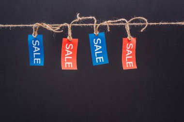 Close-up view of red and blue sale tags hanging on rope isolated on black, Offer sale tags stock vector