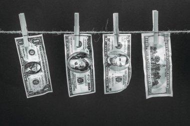 Dollar banknotes hanging on rope