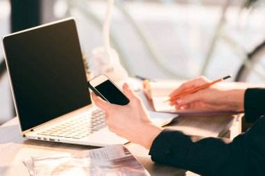 Businesswoman using laptop and smartphone