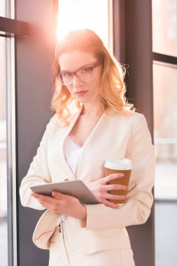 businesswoman holding digital tablet and coffee