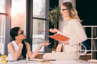 multiethnic businesswomen in formalwear talking at office