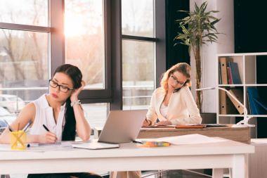 multiethnic businesswomen in formalwear working at office