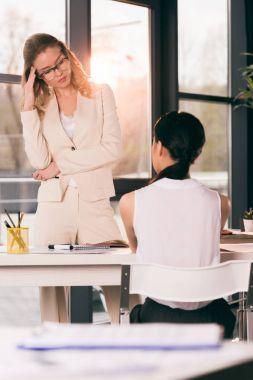 businesswomen in formalwear talking at office