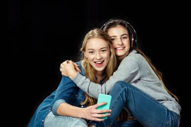 girls using smartphone and embracing