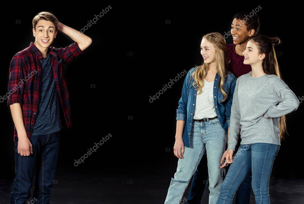 teens looking at bewildered young boy