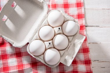 Close-up top view of raw chicken eggs in egg box on checkered tablecloth stock vector