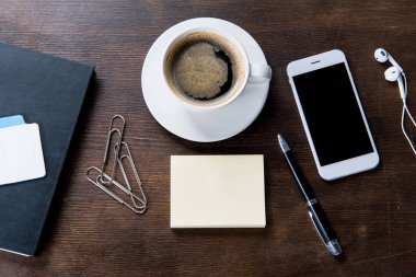 Coffee cup and smartphone on desk
