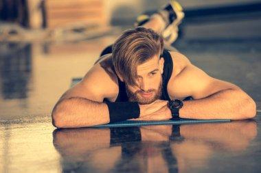 Sportsman lying on mat