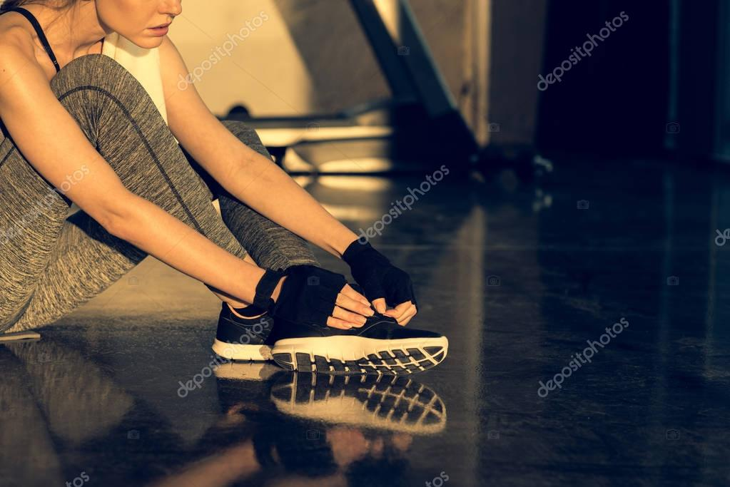 tired sportswoman sitting on floor
