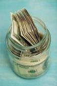 Dollar banknotes in glass jar